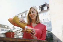Smiling blond woman with fried sausage outdoors — Stock Photo