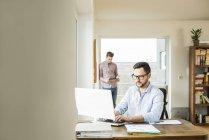Giovane uomo che lavora al computer a casa con giovane uomo sullo sfondo — Foto stock