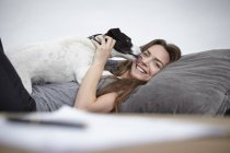 Young woman playing with dog on couch — Stock Photo