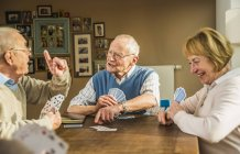 Senior friends playing cards at wooden table — Stock Photo