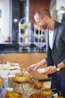 Geschäftsmann nimmt Essen vom Frühstücksbuffet — Stockfoto