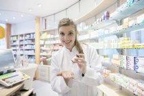 Jovem farmacêutico em farmácia apresentando medicina — Fotografia de Stock