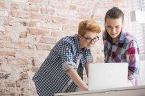 Два молодих жінок в кабінеті працюють на ноутбук — стокове фото