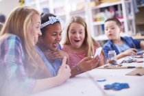 Erstaunt Mädchen in Kunst Klasse Blick auf Handy — Stockfoto