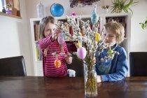 Hermano y hermana desacrando el ramo de Pascua - foto de stock