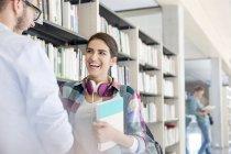 Dois alunos rindo na biblioteca universitária — Fotografia de Stock