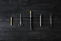 Row of different tools on black wood — Stock Photo