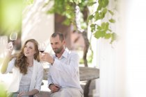 Couple sitting outdoors and tasting red wine — Stock Photo