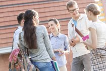 Group of young students talking outdoors — Stock Photo