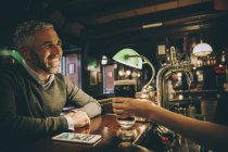 Smiling man sitting at counter of a pub — Stock Photo
