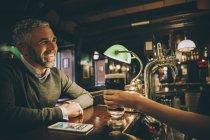Homme souriant, assis au comptoir d'un pub — Photo de stock