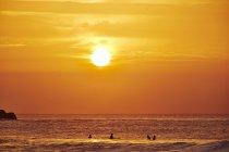 Tramonto e surfisti in linea — Foto stock