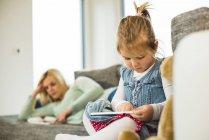 Девушка, использующая цифровой планшет на диване с мамой в фоновом режиме — стоковое фото