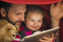 Father and daughter using digital tablet under blanket — Stock Photo