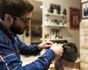Hairdresser shaving young male hair in a barbershop — Stock Photo