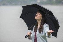Молода жінка тримає парасольку дощем — стокове фото