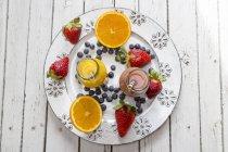 Smoothie orange et aux fraise dans des bouteilles en verre et fruits sur plaque — Photo de stock