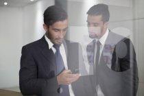 Zwei Geschäftsleute in Büro Blick auf Handy — Stockfoto