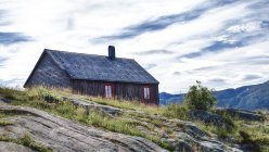 Norway, Nordland, Romsdal, wooden house on hills — Stock Photo