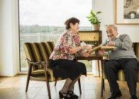 Senior couple watching photo album at home — Stock Photo