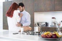 Couple dans la cuisine, partager un moment d'intimité — Photo de stock