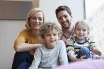 Porträt von happy Family im Fenster — Stockfoto