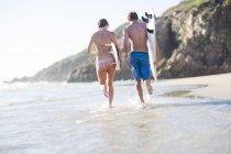 Молода пара, біг з їх дошки для серфінгу на пляжі — стокове фото