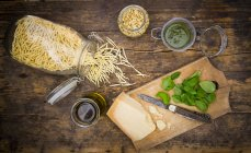 Pesto Genovese, basil leaves, parmesan, pine nuts, olive oil and raw trofie noodles on wooden table, top view — Stock Photo