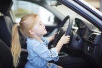 Girl at car dealer inside car steering — Stock Photo