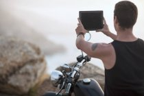 South Africa, Cape Town, motorcyclist at the coast taking pictures with digital tablet — Stock Photo