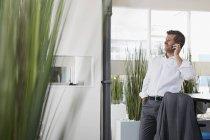 Uomo d'affari in ufficio su smartphone — Foto stock