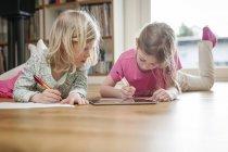 Due sorelle con tablet digitale e fogli di carta sul pavimento — Foto stock