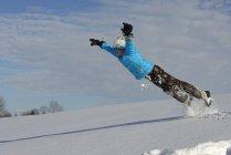 Menino se divertindo na neve durante o dia — Fotografia de Stock