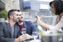 Gay couple sharing a meal and friend taking photos with cell phone — Stock Photo