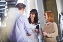 Two women and man with wine bottle shaking hands — Stock Photo