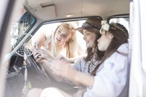 Friends on a road trip sharing mobile phone — Stock Photo