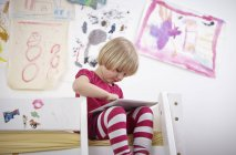 Little girl sitting on bunk bed, drawing on touch pad — Stock Photo