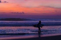 Indonésie, Bali, Surfer, marchant sur la plage au coucher du soleil — Photo de stock