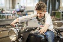 Menino fingindo dirigir vintage ciclomotor — Fotografia de Stock