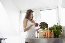 Glückliche junge Frau in der Küche mit Kiste voll mit frischem Gemüse — Stockfoto