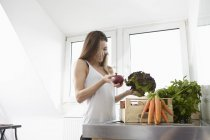 Happy young woman in kitchen with crate full of fresh vegetables — Stock Photo