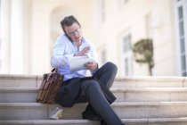 Businessman talking on phone, sitting outdoors at daytime — Stock Photo