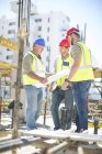 Construction workers discussing building plans in construction site — Stock Photo
