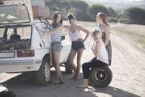 Друзі по дорозі поїздки, маючи пробою автомобіля — стокове фото
