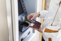 Cropped image of Woman at cash machine — Stock Photo
