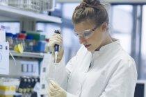 Biologiste travaillant en laboratoire avec pipette — Photo de stock