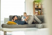 Father and daughter with digital tablet on sofa — Stock Photo