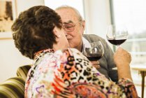 Kissing senior couple with glasses of red wine — Stock Photo