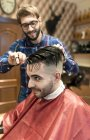 Hairdresser cutting young man's hair in a barbershop — Stock Photo