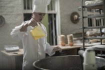 Female baker pouring ingredient into mixer — Stock Photo